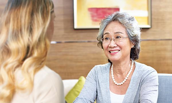 外国人と会話するシニア層の女性